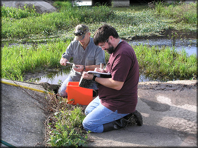 Patrick and his student record the measurements of the shells found in the ditch